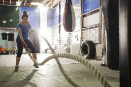 Woman exercising with ropes in gym