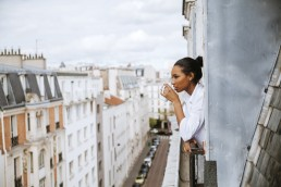 France, Paris, young woman with cup of coffee leaning out of window