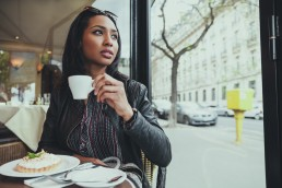 Portrait of young woman sitting in a cafe drinking coffee