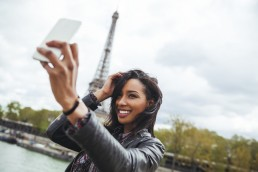 France, Paris, Young woman taking smart phone selfie in front of Eiffel Tower
