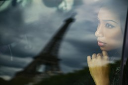 France, Paris, portrait of young woman watching Eiffel Tower through car window
