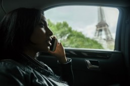 France, Paris, young woman telephoning in a car