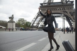 France, Paris, young woman hailing a taxi in front of Eiffel Tower