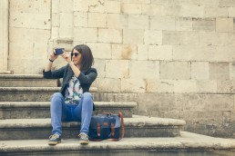 Croatia, Dubrovnik, tourist sitting on steps of Church of the Assumption taking photo