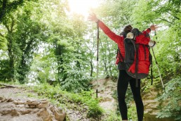 Serbia, Rakovac, young girl hiking and raising her arms in happiness