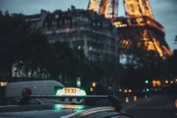 France, Paris, taxi on the stree with the view of the Eiffel Tower in the background