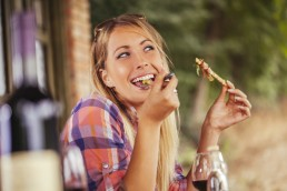Smiling woman eating outdoors