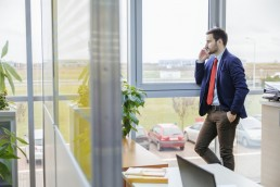 Young businessman on cell phone in office