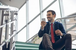 Smiling businessmann sitting on stairs using cell phone