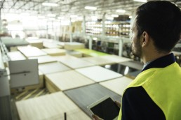Man holding tablet overlooking warehouse