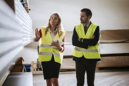 Man and woman in warehouse supervising stock